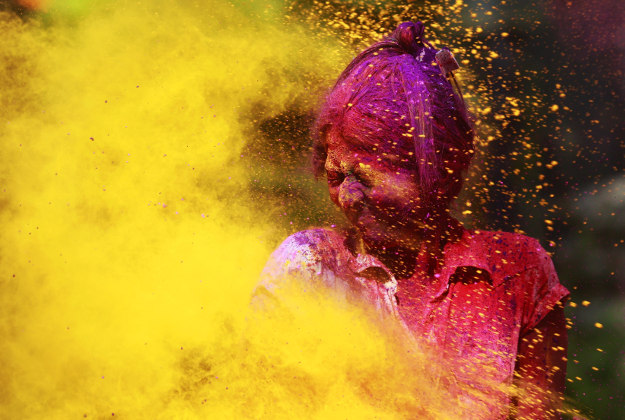 An Indian girl reacts as colored powder is smeared on her during celebrations marking Holi, the Hindu festival of colors, in Mumbai India, Thursday, March 24, 2016. The festival heralds the arrival of spring.