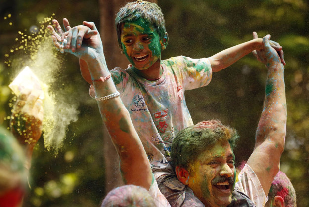 A father and his on on his shoulder with their faces smeared with colored powder celebrate Holi in Mumbai India, Thursday, March 24, 2016. Indians on Thursday celebrated Holi, the riotous annual celebration of color, that marks the end of winter and the arrival of spring. People armed with water balloons, colored water and powder in multiple hues played Holi by smearing each other's faces with color.