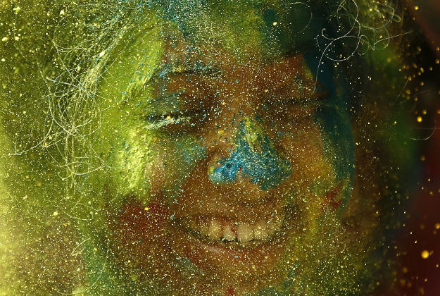 An Indian girl with her face smeared with colored powder smiles during Holi celebrations in Mumbai India, Thursday, March 24, 2016. Indians on Thursday celebrated Holi, the riotous annual celebration of color, that marks the end of winter and the arrival of spring. People armed with water balloons, colored water and powder in multiple hues played Holi by smearing each other's faces with color.