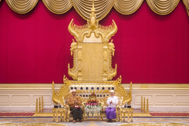 New Myanmar President Htin Kyaw, left, receives the presidential sash from outgoing president Thein Sein during a handover ceremony at the presidential palace in Naypyidaw on Wednesday, March 30, 2016. Htin Kyaw, a trusted friend of Nobel laureate Suu Kyi, took over as Myanmar's president Wednesday, taking a momentous step in the country's long-drawn transition toward democracy after more than a half-century of direct and indirect military rule.