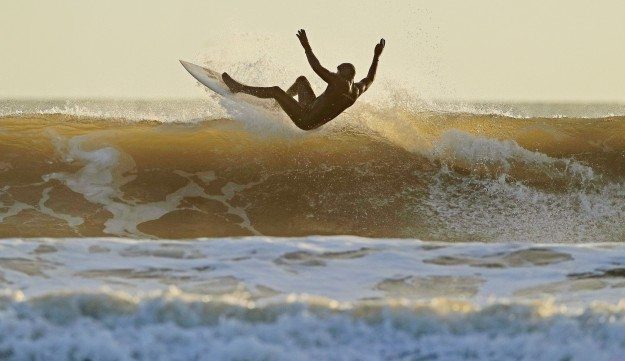 A surfer in action at Tynemouth, Tyne and Wear, at sunrise.