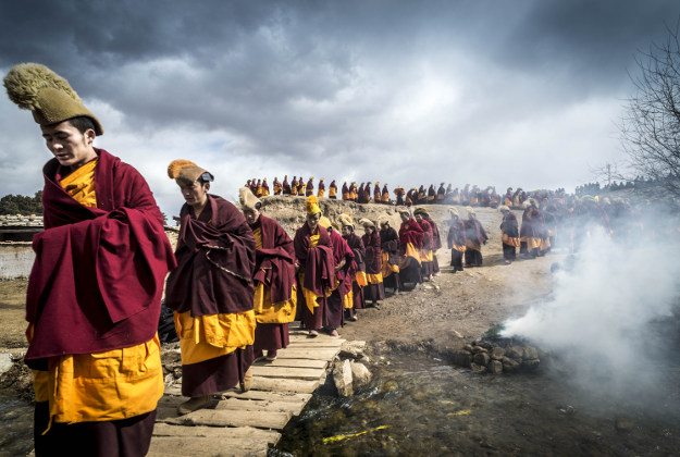 """The great prayer festival of Monlam takes place in eastern Tibet during the heart of winter. Tens of thousands of pilgrims join the monks in celebrating the event. Here the monks of Taktsang Lhamo are performing the ritual known as the 'Turning of the Buddha' where a statue of the Maitreya Buddha is carried around the four corners of the village. Maitreya is a Buddha who will appear on Earth in the future, achieve complete enlightenment and then teach the dharma. This ceremony is to ensure that the earthly realm will be ready for his arrival."""