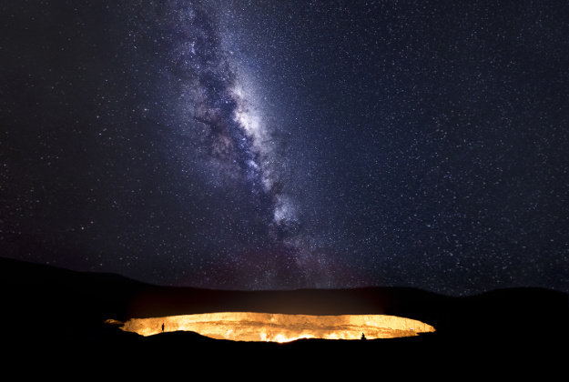 """The milky way galaxy rises over the Darwaza crater in the Karakum desert, northwest Turkmenistan. Two explorers peer into its fiery depths, known by the local Turkmen as the 'door to hell'. In 1971 Soviet scientists discovered an underground cavern with gas accumulation. It was set on fire to avoid a toxic release into nearby villages and in the hope it would burn out within days to, yet 45 years later, it continues to burn. Often described as the world's most beautiful ecological disaster. Karakom desert, Turkmenistan"""