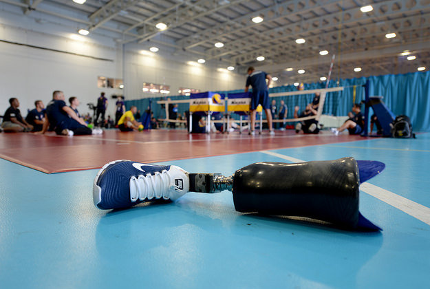 A prosthetic leg sits beside the volleyball court as the U.S. Invictus Games seated volleyball team practices for competition.