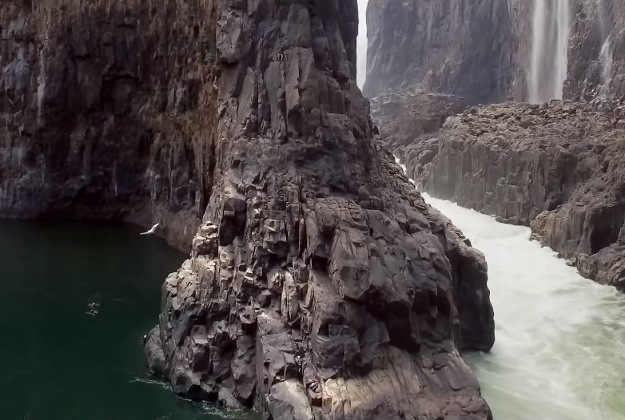 Two cliff divers leap from Victoria Falls in Africa.