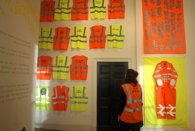 A woman looks at an artwork  by Petro called Utopia Security Co.High Visibility Graffito solutions