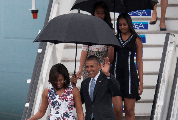 President Barack Obama waves from Air Force One as he arrives accompanied by first lady Michelle Obama and daughters Sasha, right, and Malia at Jose Marti International Airport in Havana, Cuba, Sunday, March 20