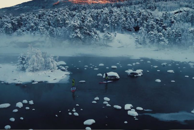 The girls stand up paddle boarding through the Norwegian landscape