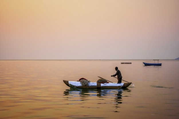 Sunset fishing from canoe on the Lake of Stars (Lake Malawi), Cape Maclear .