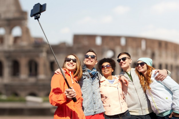 Group of smiling teenage friends taking selfie with smartphone and monopod with Coliseum ruins in background.