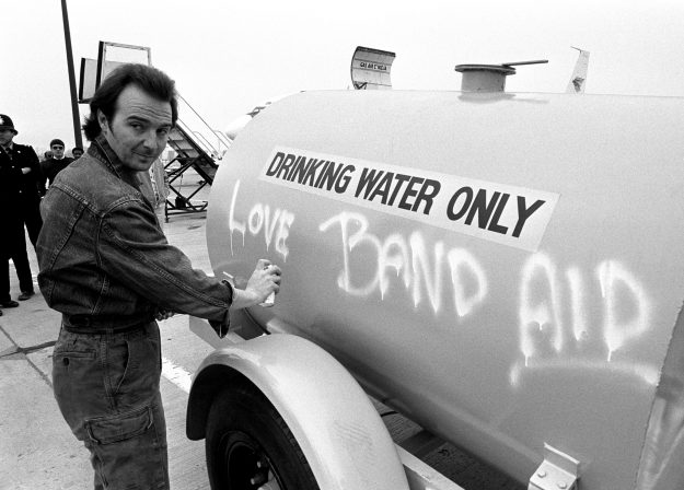 Midge Ure, 31 of the Rock Group Ultravox, who with Bob Geldof wrote the Band Aid single 'Do They Know It's Christmas?', spraying a message on a water tanker at Gatwick Airport.