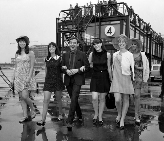 Bob Monkhouse joins 'The Beat Girls' at Gatwick Airport.