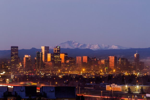 Denver city skyline photographed before sunrise with Pikes Peak Behind
