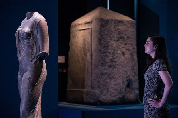 Kate Morais looks at the statue of 'Arsinoe II, queen and goddess' (300BC) next to the 'Shrine of Amun-Gereb' (400-100BC) during a preview of the 'Sunken Cities: Egypt's Losts Worlds' exhibiton at the British Museum on May 17, 2016 in London, England. This is the museum's first large scale exhibition of underwater archaelogical finds and tells the story of two lost Egyptian cities and their recent discoveries beneath the Mediterranean, excavated off the coast of Egypt near Alexandria between 1996 and 2012.
