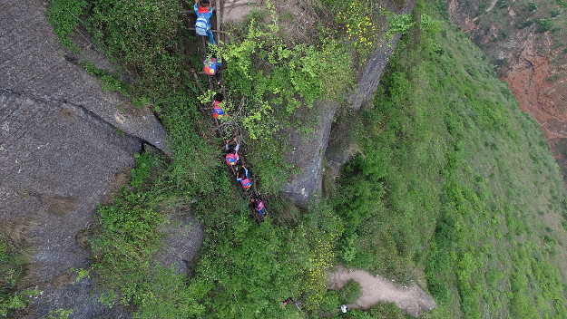 Pupils from Atuler village rest at the cliff on their way to go home after school on May 14, 2016 in Liangshan Yi Autonomous Prefecture, Sichuan Province of China. 72 families lived in Atuler village on the 800-meter cliff at Meigu River Canyon in Liangshan Yi Autonomous Prefecture. 15 pupils, aged 6 to 15, accompanied by 3 adults regularly spent 2 hours climbing 17 vines ladders hung on the 800-meter-high cliff to go between school and home twice a month. Villagers used the same ladders to go to the nearest market once a week to sell peppers and walnuts and buy necessities.