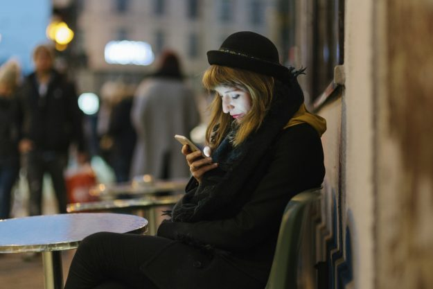 Woman sitting at outdoor cafe using mobile.