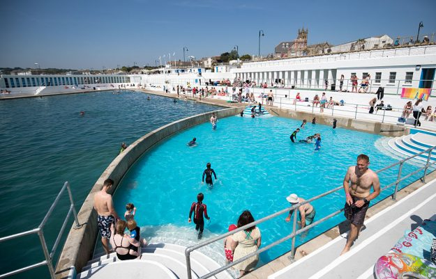 PENZANCE, ENGLAND - MAY 30: Bathers enjoy the fine weather at the recently reopened Jubilee Pool lido in Penzance on May 30, 2016 in Cornwall, England. The Grade II Listed Art Deco seaside pool that suffered structural damage in the storms of early 2014, reopened this weekend after a £3million refurbishment. The pool, the UK's largest surviving seawater pool and an iconic feature of the seafront since it first opened in 1935, has recently announced future plans to heat part of the it with geothermal energy. (Photo by Matt Cardy/Getty Images)