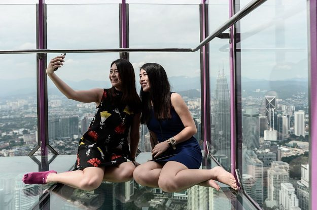 Ng Sin Nee (L) and Lee Shin May (R) from Malaysia take pictures with the panoramic view of the city from the Sky Box at KL Tower