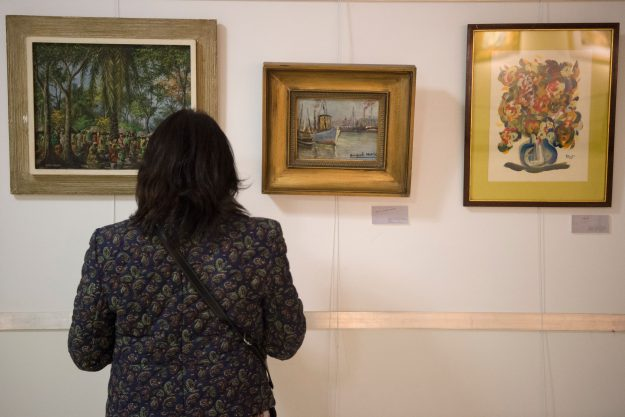 A woman looks at a forged painting by Argentina's artist Benito Quinquela Martin (C) exhibited at the Finance Ministry in Buenos Aires on April 26, 2016.