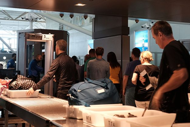 People wait in a security line operated by the TSA at JFK Airport on May 24, 2016.