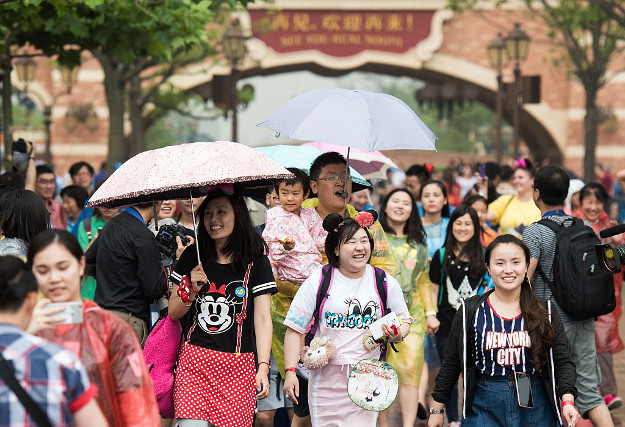 Visitors attend the opening day of the Shanghai Disney Resort in Shanghai on June 16, 2016. Entertainment giant Disney brings the ultimate American cultural concept to Communist-ruled China on June 16, opening a massive theme park in Shanghai catering to a rising middle class.