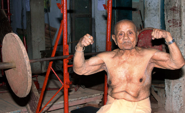 KOLKATA, INDIA – MARCH 20: Manohar Aich who recently celebrated his 100th birthday showing his biceps at his gymnasium at Baguihati resident on March 20, 2012 in Kolkata, India. Popular as Pocket Hercules for his short frame of 4 feet 11 inch, he won Mr Universe in 1952 and was three times Asian Gold Medalist for Body Building. (Photo by Ramkrishna Samanta/ Hindustan Times via Getty Images)