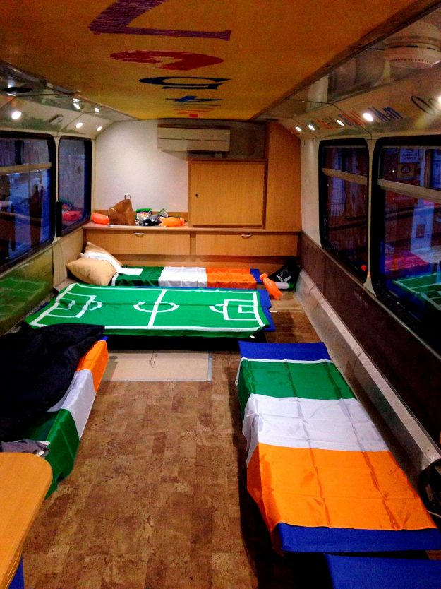 The inside of an old double-decker bus is kitted out with beds