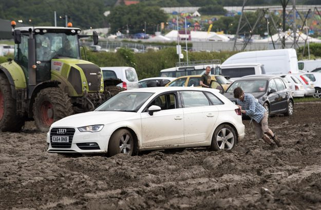 A man tries to push a car as festival goers leave the Glastonbury Festival