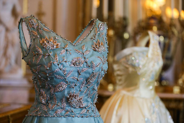 A Turquoise silk shift dress with silver floral embroidery by Hardy Amies (L) and a Pale Blue and gold evening dress by Sir Norman Hartnell.