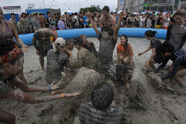 Festival-goers enjoy the mud during the annual Boryeong Mud Festival at Daecheon Beach on July 16, 2016 in Boryeong, South Korea. The mud, which is believed to have benefical effects on the skin due to its mineral content, is sourced from mud flats near Boryeong and transported to the beach by truck.