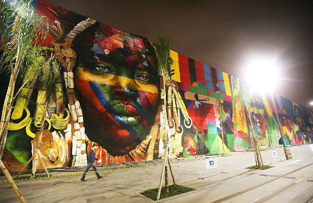 A man walks past a section of a mural depicting indigenous faces being created by Brazilian graffiti artist Eduardo Kobra and assistants in the revamped Port District on July 20, 2016 in Rio de Janeiro, Brazil. The 32,000-square-foot mural, titled 'We Are All One', is being painted to represent cultural diversity across continents and will be completed shortly before the start of the Rio 2016 Olympic Games on August 5.