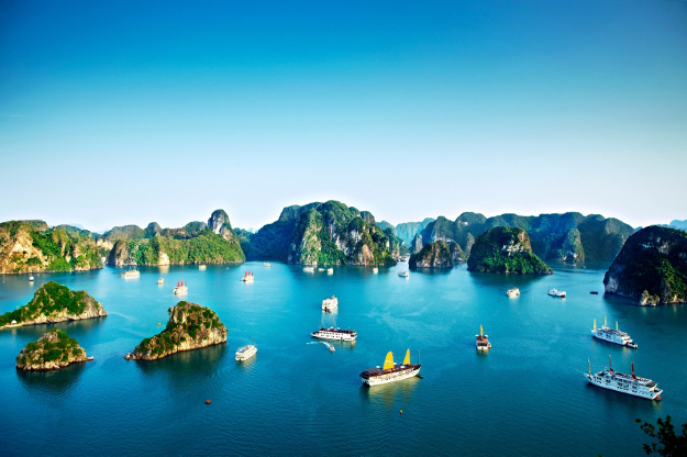 Chinese junks and cruise ships passing by limestone islands in Halong Bay.