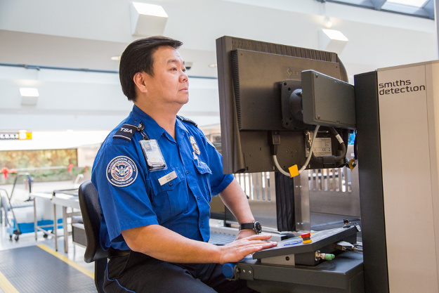 transportation security officer tso steve chao reviews baggage at washington dulles international