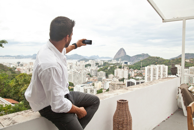Man taking photo on terrace, Sugarloaf Mountain in background, Rio, Brazil.