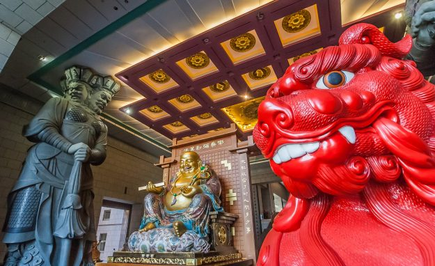 Red lion and chinese Buddha of the Chung-tai Chan monastery in Taiwan