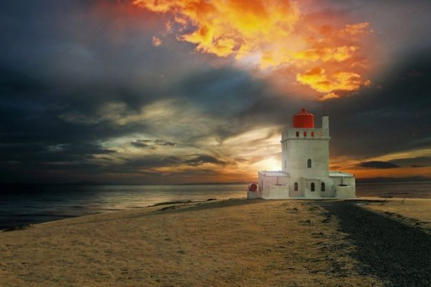 Iceland lighthouses often have dramatic architecture like this castle-like building.
