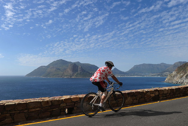A man cycles along the road near Hout Bay in Capetown.