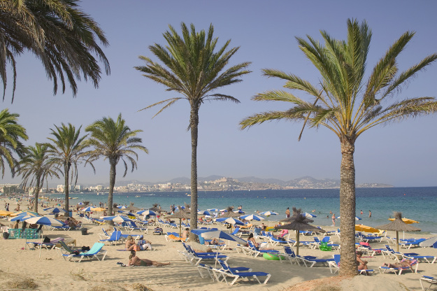 Vacationers soak up the Mediterranean sun on Playa or Platja D'en Bossa. Platja D'en Bossa is one of the longest beaches on Ibiza, and features over 50 beachfront bars.