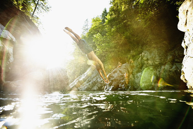 Man diving off boulder into river swimming hole with friends watching from opposite side.