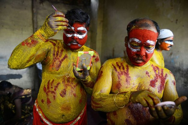 Devotees Kannaih Goud (L) and Madan Singh Yadav dress as Potharaju, brother of the Hindu goddess Maha Kali, before performing in a final procession.