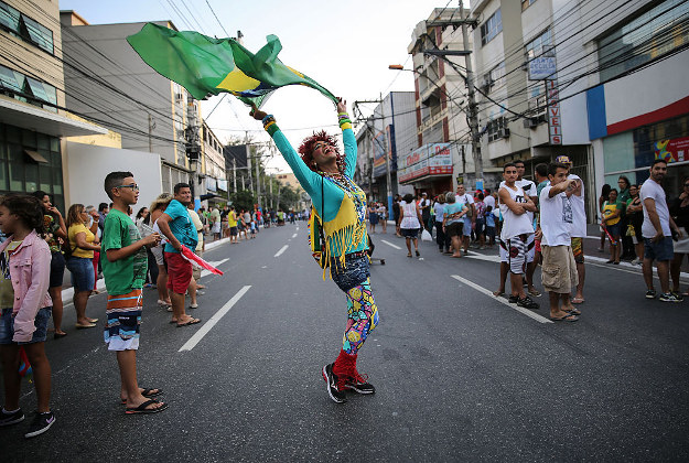 A fan waves a Brazilian flag before the arrival of the Olympic torch ahead of the Rio 2016 Olympic Games on August 2, 2016 in Sao Goncalo, Rio de Janeiro state, Brazil. The torch will arrive in the city of Rio tomorrow and the Games commence on August 5.