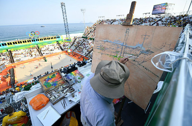 An artist paints the scene during the men's beach volleyball qualifying match between Latvia and Cuba at the Beach Volley Arena in Rio de Janeiro on August 9, 2016, during the Rio 2016 Olympic Games.