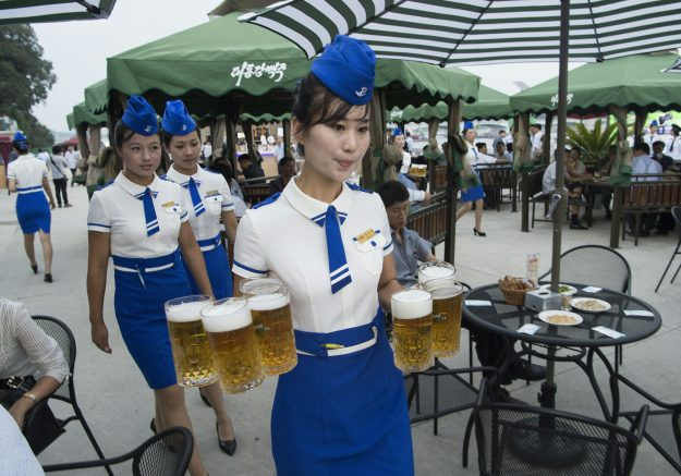 A waitress carries jugs of beer to guests before the opening of the Pyongyang Taedonggang Beer Festival on the banks of the Taedong river in Pyongyang