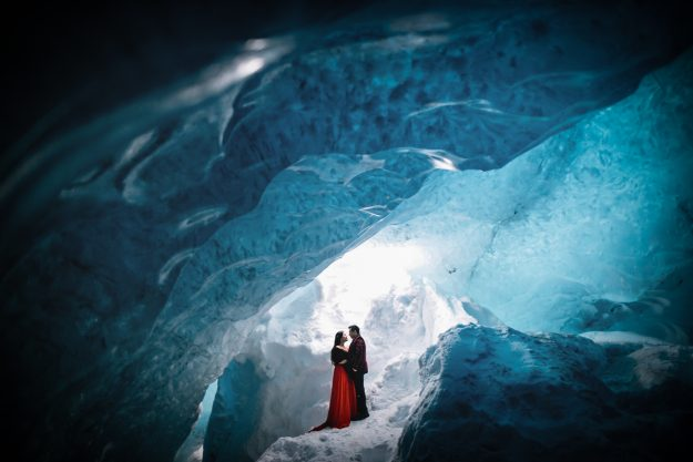 The couple pose in the glacier lagoon as part of their dramatc Iceland engagement shoot.