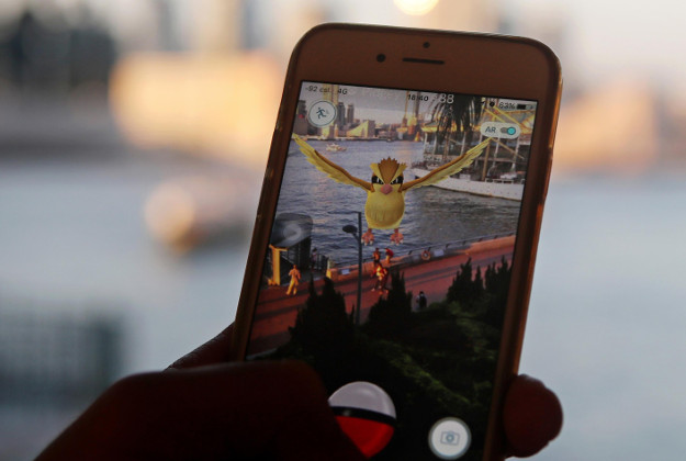 "A fan maneuvers his smartphone as he plays ""Pokemon Go"" in Hong Kong, Monday, July 25, 2016. Pokemon fans used the app on Monday as it was released to both iPhone and Android users. (AP Photo/Kin Cheung)"