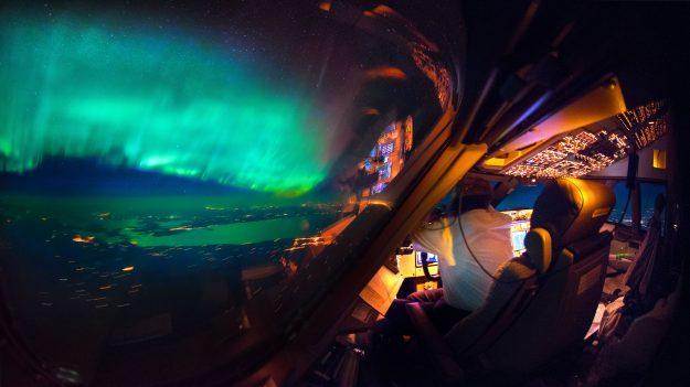 An amazing view of the Northern Lights from the cockpit of a plane.