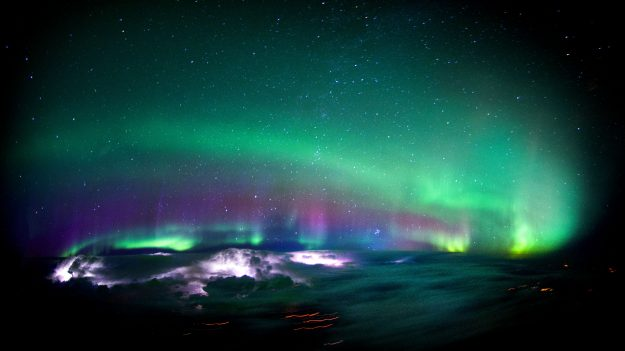 Lightning lights up inside some clouds as the Northern Lights cover the sky above it.