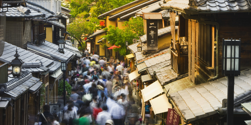 Tourists fill a street lined with traditional wooden houses near Kiyomizu-dera, one of Kyoto's most popular shrines.