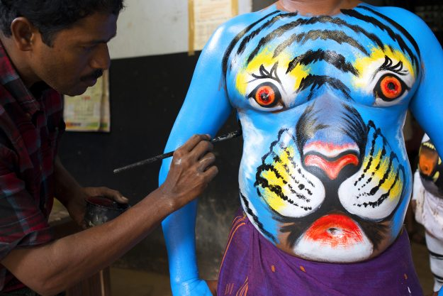 An artist paints a man's belly in vibrant colours in preparation for the event.