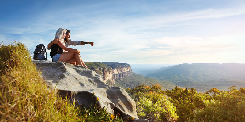 Young traveling couple having rest on the rock and enjoying view in Blue Mountains in Australia.